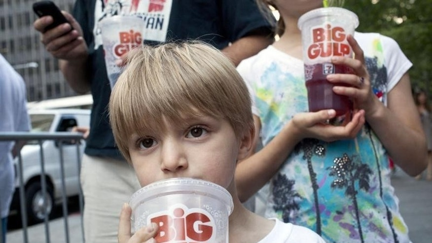 "Benjamin Lesczynski, 8, of New York, takes a sip of a ""Big Gulp"" while protesting the proposed ""soda-ban,"" that New York City Mayor Michael R. Bloomberg has suggested, outside City Hall in New York July 9, 2012.  REUTERS/Andrew Burton"