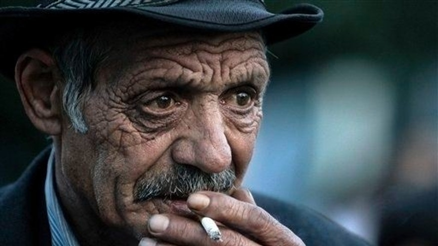 An elderly man smokes.