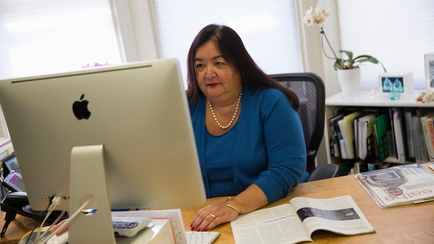 "FILE - In this March 24, 2014, file photo, Jane Delgado, president of the National Alliance for Hispanic Health, works in her office in Washington. A change in government procedures has led to a big jump in people losing coverage under the Obama health care law because of immigration and citizenship issues. ""Same dog, different collar,"" said, evoking an old Spanish saying about situations that do not seem to change (AP Photo/ Evan Vucci, File)"