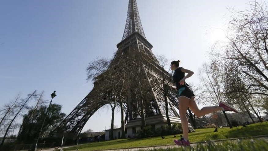 A jogger enjoys a run near the Eiffel Tower on a warm and sunny day in Paris April 8, 2015.   REUTERS/Gonzalo Fuentes