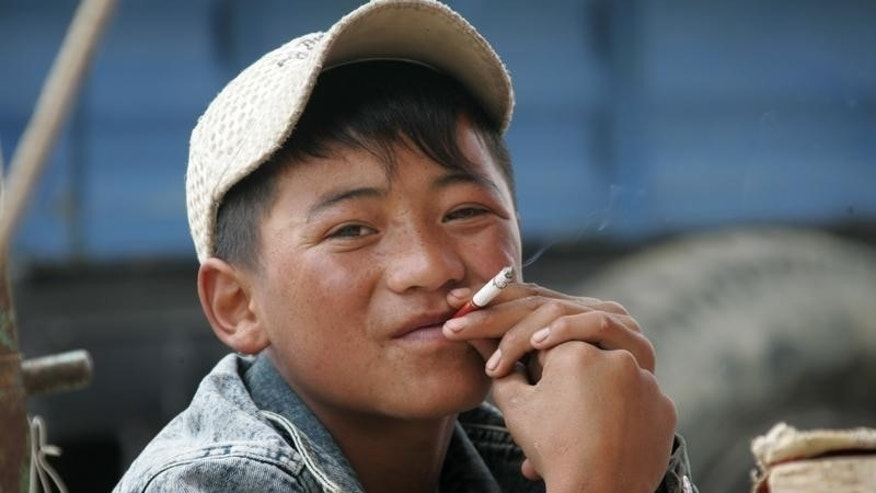 A 16-year-old Tibetan boy smokes in Dangxiong country, Tibet, June 29, 2006.   REUTERS/Jason Lee