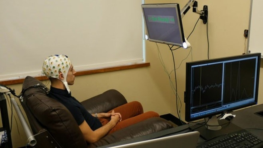 University of Washington graduate student Jose Ceballos wears an electroencephalography (EEG) cap that records brain activity and sends a response to a second participant over the Internet.