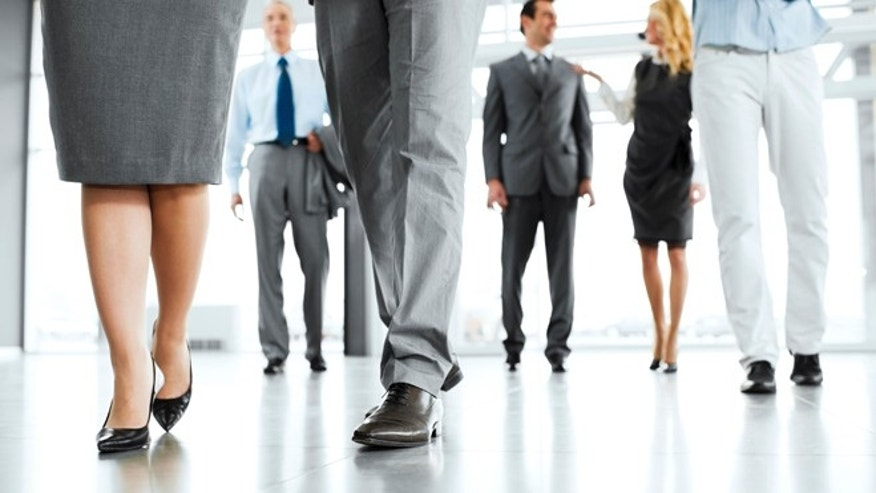 Businesspeople entering the building.  The focus is on the human legs in the foreground. 