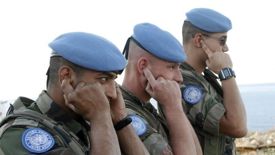 French U.N. peacekeepers (UNIFIL) cover their ears during the live training exercise between Lebanese army and U.N. peacekeepers near the United Nations Interim Force in Lebanon (UNIFIL) headquarters in Naqoura, southern Lebanon, December 4, 2008. REUTERS/Haidar Hawila