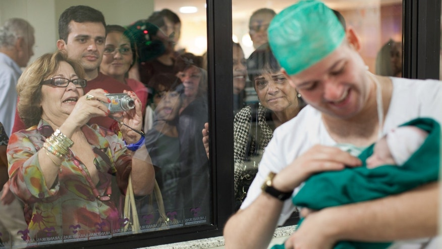 FILE - In this Aug. 2, 2012 file photo, relatives watch as Romulo Coelho holds his newborn daughter, Hadassa, birthed via cesarean section at the Perinatal Clinic in Rio de Janeiro. In clinics like Perinatal, most new parents have medical insurance that cover the $4,200 price tag of the C-sections, plus a three-day stay in a private room. But that cost can rise considerably. (AP Photo/Felipe Dana, File)