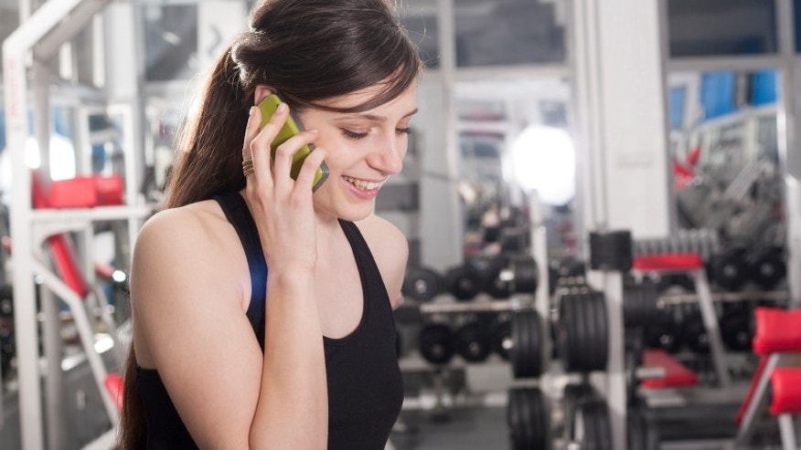 sporty girl talking by the mobile phone in gym
