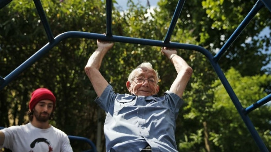 In this Tuesday, June 17, 2014 photo, George Jackson, 85, an army veteran and former boxer swings on monkey bars as he participates at a parkour class for elderly people at a park in south London. (AP Photo/Lefteris Pitarakis)