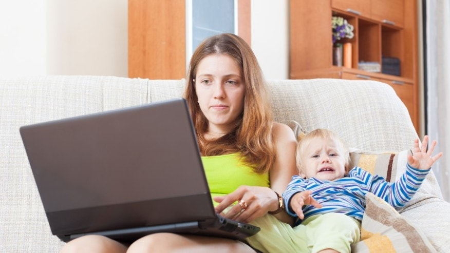 sorehead mother with crying toddler working online with laptop at home