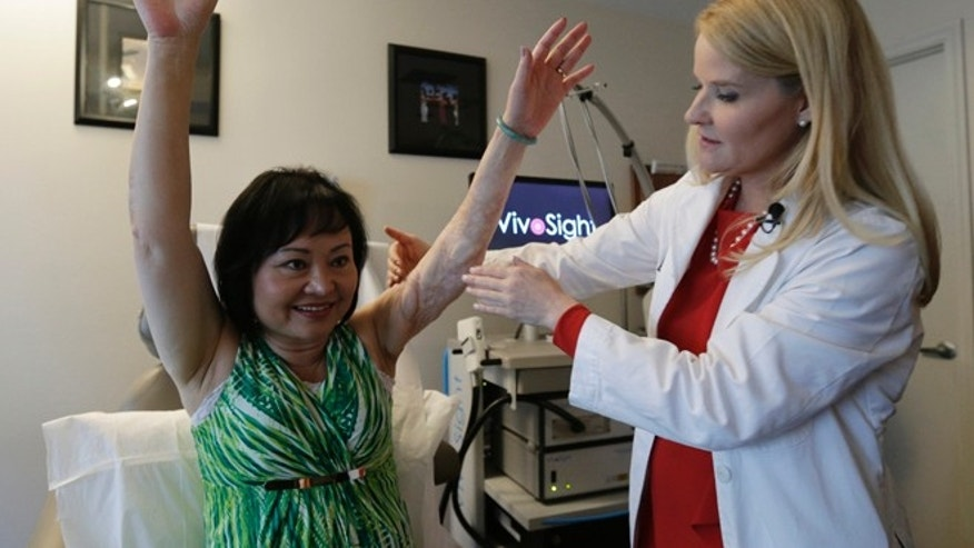 Sept. 26, 2015: Dr. Jill Waibel examines Kim Phuc before the first of several laser treatments to reduce pain and the appearance of burn scars in her back and left arm in Miami. Phuc was injured by a napalm bomb in Vietnam 40 years ago.