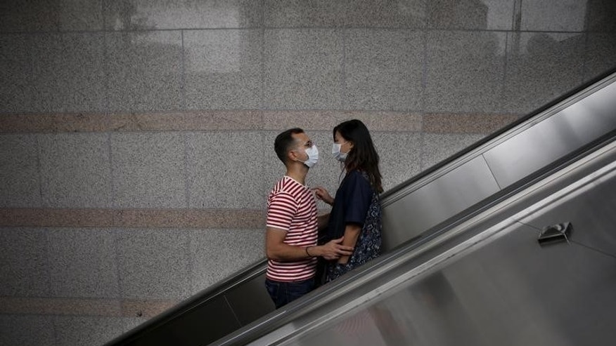 A couple wearing masks to prevent contracting Middle East Respiratory Syndrome (MERS) looks at each other as they ride on an escalator in Seoul, South Korea, June 11, 2015. REUTERS/Kim Hong-Ji