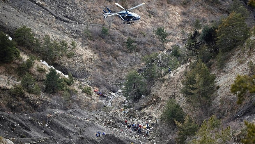 FILE - In this Thursday March 26, 2015 file photo, a helicopter flies over rescue workers at the crash site of the Germanwings jet near Seyne-les-Alpes, France. The somber mission to recover the remains of 150 people killed instantly when the Germanwings flight slammed full speed into the Col de Mariaud is not a quiet one and crucial physical evidence for the crash investigation can be gathered only when the mountains cooperate. (AP Photo/Laurent Cipriani, File)
