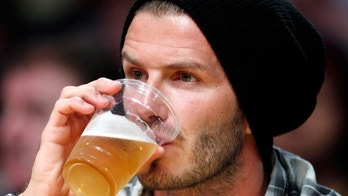 Soccer player David Beckham sips on a beer as he sits courtside with his foot in a cast during Game 2 of the NBA Western Conference playoff series between the Los Angeles lakers and the Oklahoma City Thunder in Los Angeles, April 20, 2010.