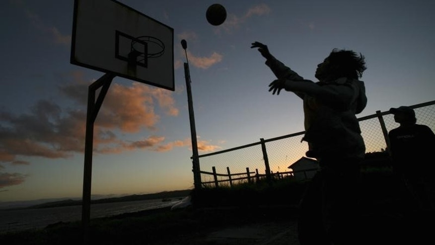 A boy plays basketball by the shore of Melinka's bay in the El Corcovado Gulf, Aysen Region, about 1,200 km (754 miles) south of Santiago, March 25, 2008. REUTERS/Ivan Alvarado