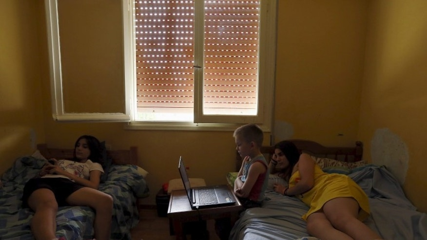 Anthoula Papazoi's son Anastasis, (C), 5, watches a DVD in the bedroom shared by his sisters Nikoleta (L), 13, and Elli, 16, at their home in the city of Ioannina, Greece July 10, 2015. Picture taken July 10, 2015.  REUTERS/Cathal McNaughton
