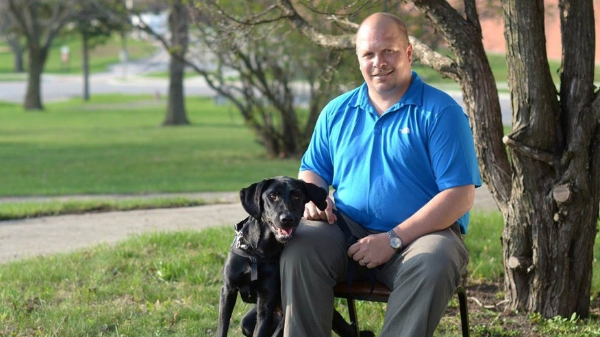 In this March 2012 photo provided by Paws & Effect, Wade Allen Baker sits with Honor at the end of the PTSD service dog's placement with him and the workshop that all recipients go through at Camp Dodge in Johnston, Iowa. (Todd Cerveris/Paws & Effect via AP)