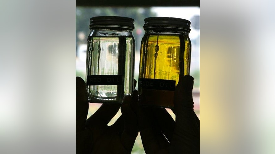 Jars of clear, processed safflower oil, left, and unprocessed oil, right are displayed.