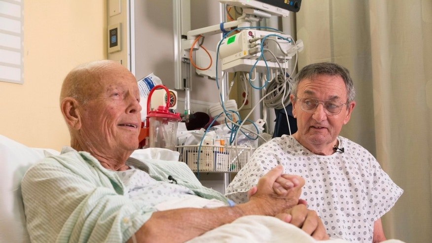 "In this Nov. 5, 2015 photo, Henry ""Bill"" Warner, left, and John Middaugh clasp hands prior to their surgeries at NewYork-Presbyterian/Weill Cornell Medical Center in New York. (AP Photo/Mark Lennihan)"