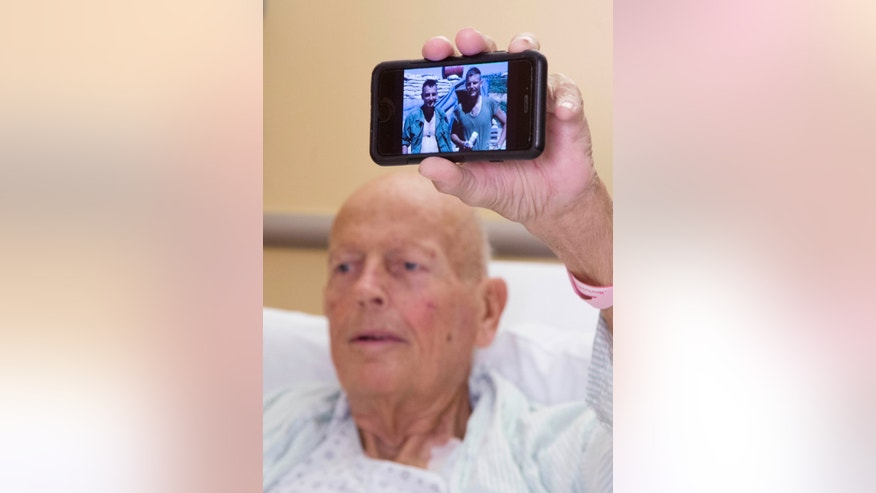 "In this Nov. 5, 2015 photo, Henry ""Bill"" Warner holds up a cell phone to show a photo of himself and Vietnam War buddy John Middaugh, prior to his kidney transplant surgery in New York. (AP Photo/Mark Lennihan)"