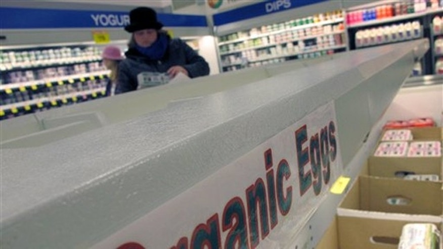 In this Dec. 6 photo, a shopper picks up a box of brown eggs at a grocery store in Urbana, Ill.