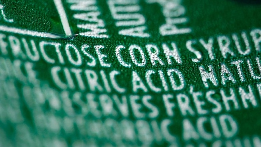 FILE - This Sept. 15, 2011 file photo shows a nutrition label that lists high fructose corn syrup as an ingredient in a can of soda, in Philadelphia. In a trial starting Tuesday, Nov. 3, 2015, jurors in the case between sugar processors and corn manufacturers will take up one of nutritionâs most vexing debates and confront a choice common among some consumers: sugar or high fructose corn syrup? (AP Photo/Matt Rourke, File)