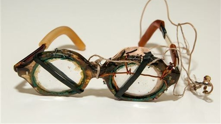A file photo of eyeglasses held together by string, wire and rubber bands.