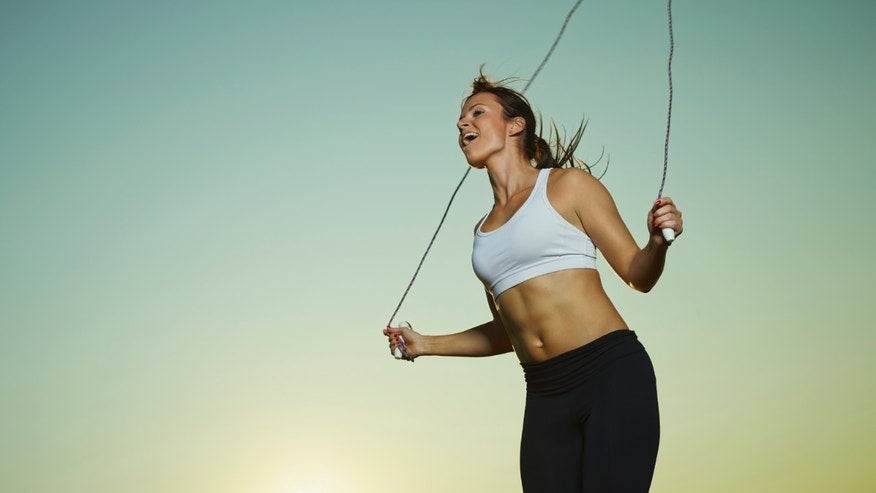 Young fitness woman used a skipping rope, sun and sky on background, copy space
