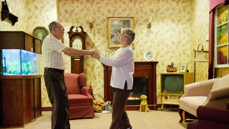 Decima Assise, who has Alzheimer's disease, and Harry Lomping dance to old music in a replica mid 1900s living room Friday, Nov. 6, 2015, at The Easton Home in Easton, Pa. Nursing homes and assisted living facilities are increasingly using sight, sound and other sensory cues to stimulate memory in people with Alzheimer's disease and other forms of dementia. (AP Photo/Matt Rourke)