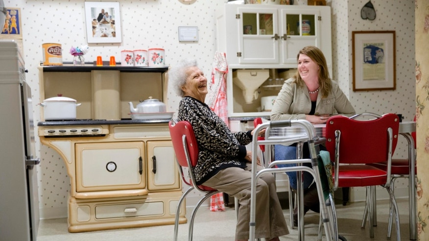 Olga Deacon, who has dementia, speaks with her granddaughter, Chris Boyce, in a replica 1940s kitchen, Friday, Nov. 6, 2015, at The Easton Home in Easton, Pa. Nursing homes and assisted living facilities are increasingly using sight, sound and other sensory cues to stimulate memory in people with Alzheimer's disease and other forms of dementia. (AP Photo/Matt Rourke)
