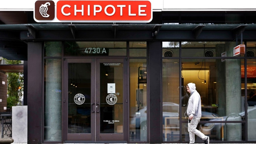A pedestrian walks past a closed Chipotle restaurant Monday, Nov. 2, 2015, in Seattle. An E. coli outbreak linked to Chipotle restaurants in Washington state and Oregon has sickened nearly two dozen people in the third outbreak of foodborne illness at the popular chain this year. Cases of the bacterial illness were traced to six of the fast-casual Mexican food restaurants, but the company voluntarily closed down 43 of its locations in the two states as a precaution. (AP Photo/Elaine Thompson)