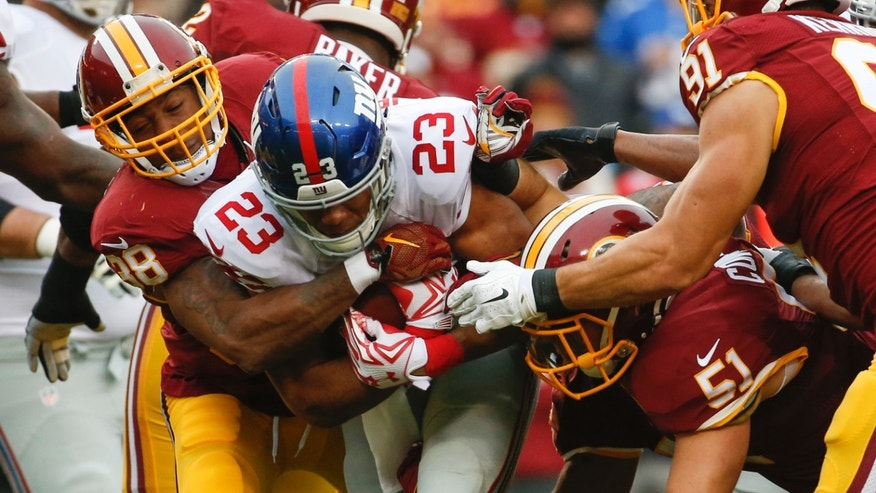New York Giants running back Rashad Jennings (23) is stopped by Washington Redskins free safety Dashon Goldson (38) and inside linebacker Will Compton (51) during the first half of an NFL football game in Landover, Md., Sunday, Nov. 29, 2015. (AP Photo/Alex Brandon)