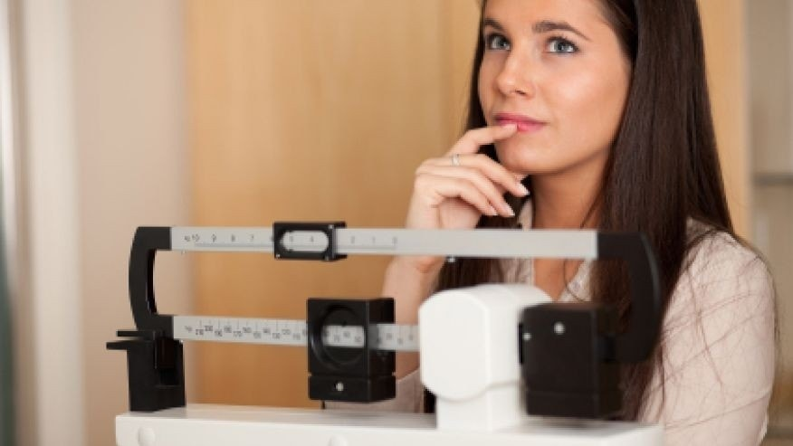 young woman on scale istock