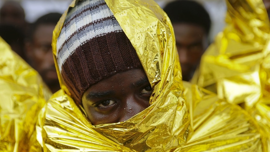 A migrant waits to disembark from a Coast Guard ship in the Sicilian harbour of Messina, Italy August 4, 2015. REUTERS/Antonio Parrinello