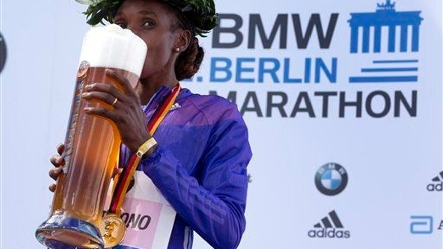 Winner Gladys Cherono tastes beer during the medal ceremony for the 42nd Berlin Marathon in Berlin on Sept. 27, 2015.