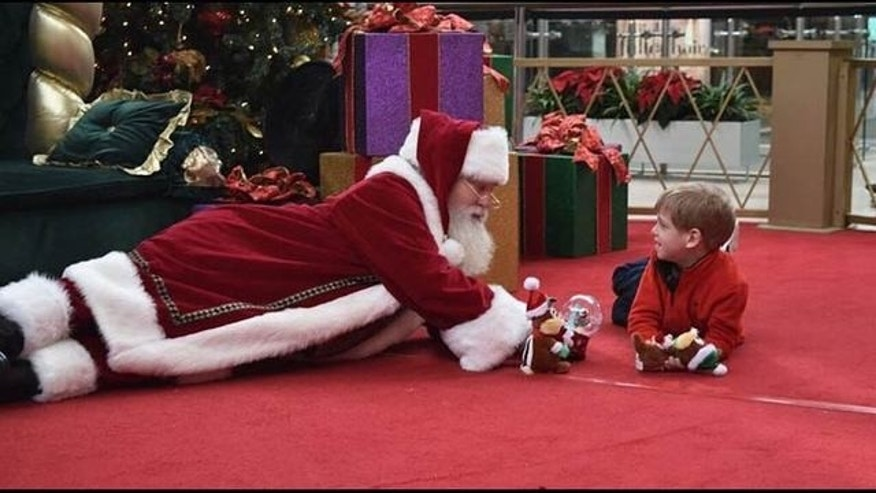 A mall Santa in Charlotte, North Carolina, who was not named by Fox 5 Atlanta, is photographed on the floor this holiday season with Brayden Deely, a 6-year-old boy with autism, to help quell the young boy's fear of strangers.