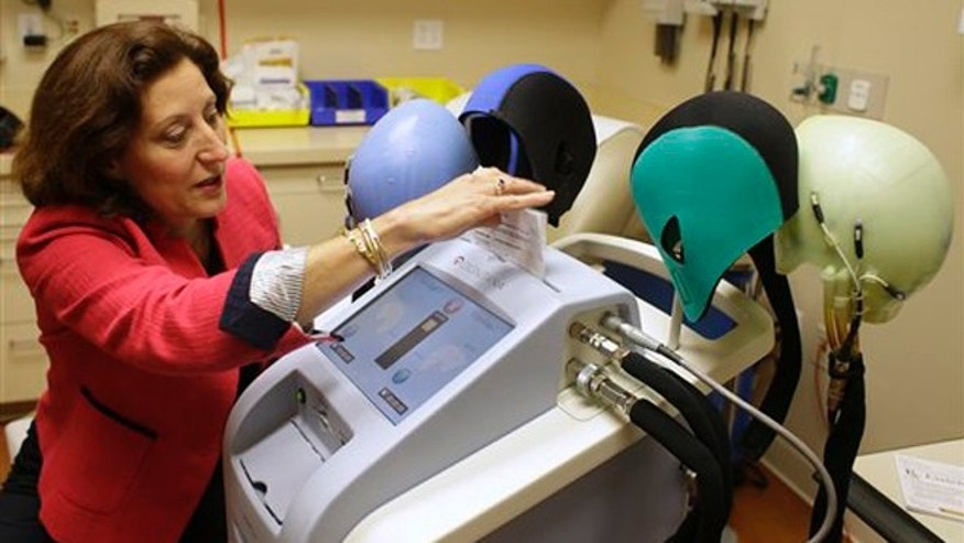 July 10, 2013: Dr. Hope Rugo, an oncologist and breast cancer specialist, demonstrates the use of a Dignitana DigniCap system at the University of California San Francisco Mount Zion Hospital cancer center in San Francisco. (AP Photo/Eric Risberg)