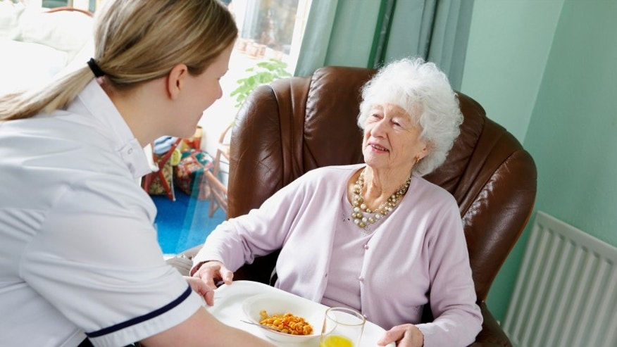 A carer helps her elderly patient.