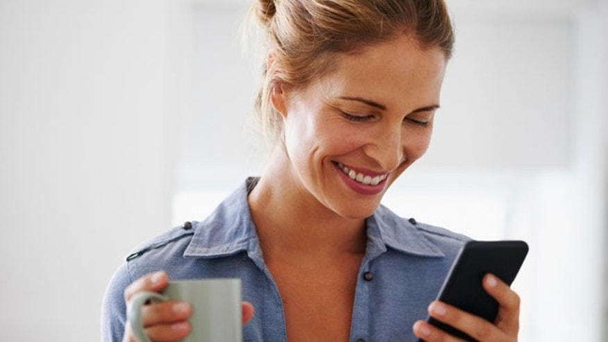 Woman drinking coffee using smartphone at home