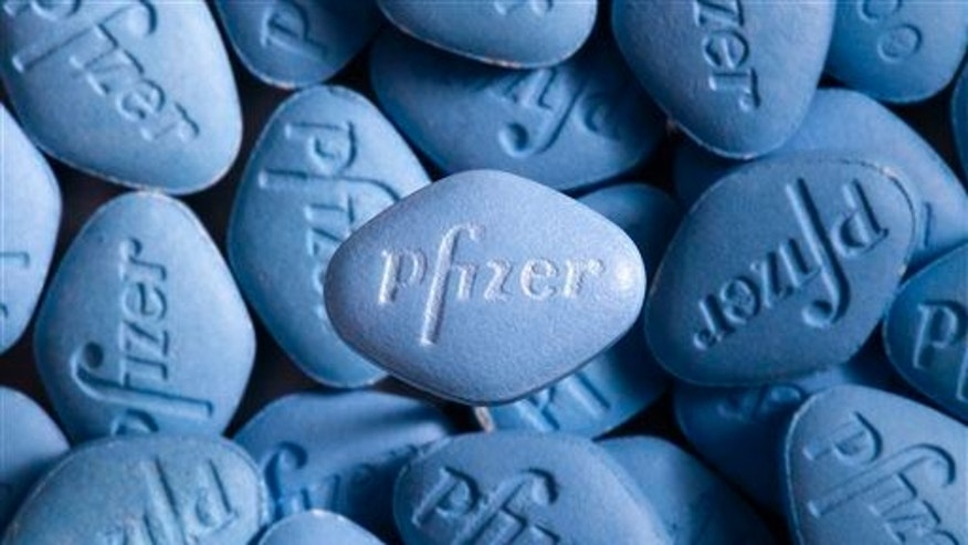 This undated photo provided by Pfizer shows a real Viagra pill on top of counterfeit pills