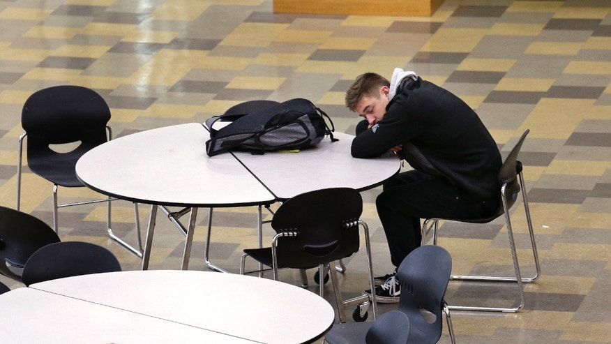 In this photo taken Nov. 23, 2015, a student leans on a table in the cafeteria during first period at Roosevelt High School in Seattle. More school districts around the U.S. are heeding the advice of scientists who have long said that expecting teens to show up to class before 8 a.m. isn't good for their health or their report cards. (AP Photo/Elaine Thompson)