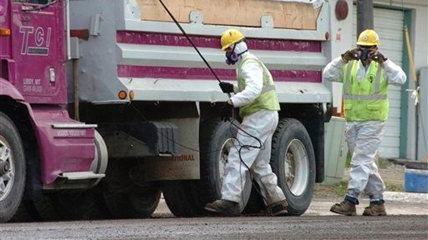 In this April 28, 2011 file photo, unidentified road workers wear protective gear against possible asbestos contamination.