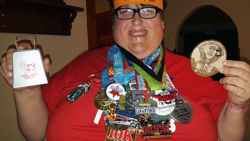 Derek Mitchell dons his collection of race medals he earned in 2015. PHOTOGRAPH COURTESY OF DEREK MITCHELL