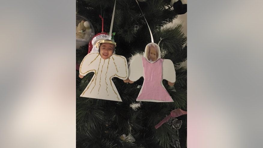 A photo shows cut-out pictures of Kyree's and Arianna's faces on Christmas ornaments.