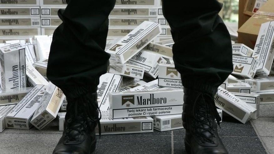 A German customs officer stands in front of confiscated cigarettes before the customs annual news conference in Munich March 13, 2007.  REUTERS/Michaela Rehle