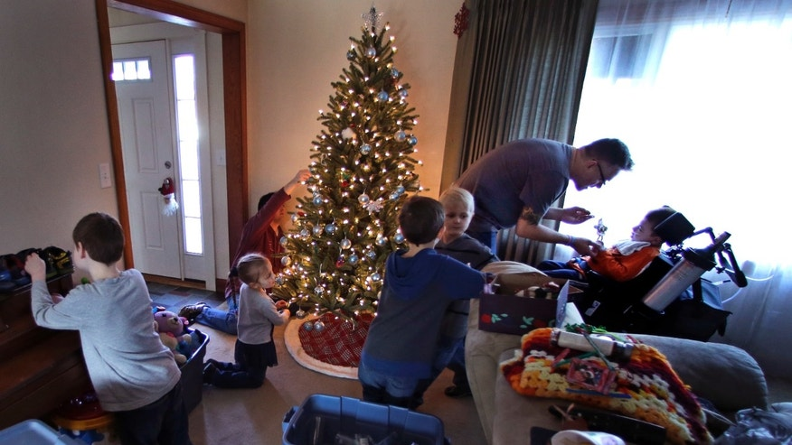 In this Saturday, Dec. 12, 2015 photo, Eric Volz-Benoit, a registered nurse who works with children afflicted with complex medical disabilities, attends to his adopted son Zachary, right, who is wheelchair-bound after being born with cerebral palsy, while Eric's partner Dennis, left rear, trims the Christmas tree at their family home in Springfield, Mass. Zachary is a patient participating in the Collaborative Consultative Care Coordinator Program, or 4C, where a team overseas all aspects of his care. (AP Photo/Charles Krupa)