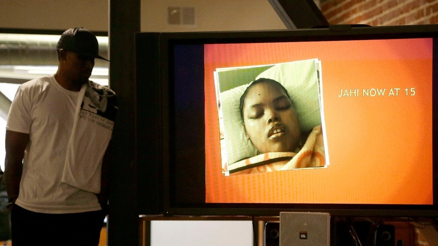 A recent photo of Jahi McMath on a video screen next to her uncle Timothy Whisenton in San Francisco, Wednesday, Dec. 23, 2015.