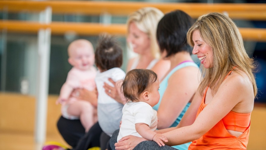 Mothers and their babies staying active and healthy by doing exercises (yoga, stretching, and aerobics) together at a health club.
