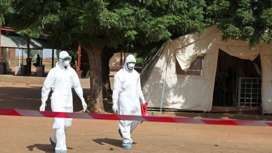 Oct. 25, 2014: Health workers walk towards an area used for Ebola quarantine after they worked with diseased Fanta Kone at a Ebola virus center in Kayes, Mali