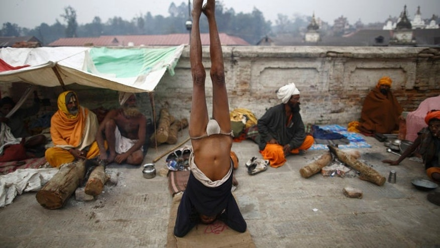 A Hindu holy man, or sadhu, performs yoga at the premises of Pashupatinath Temple in Kathmandu February 26, 2014. REUTERS/Navesh Chitrakar