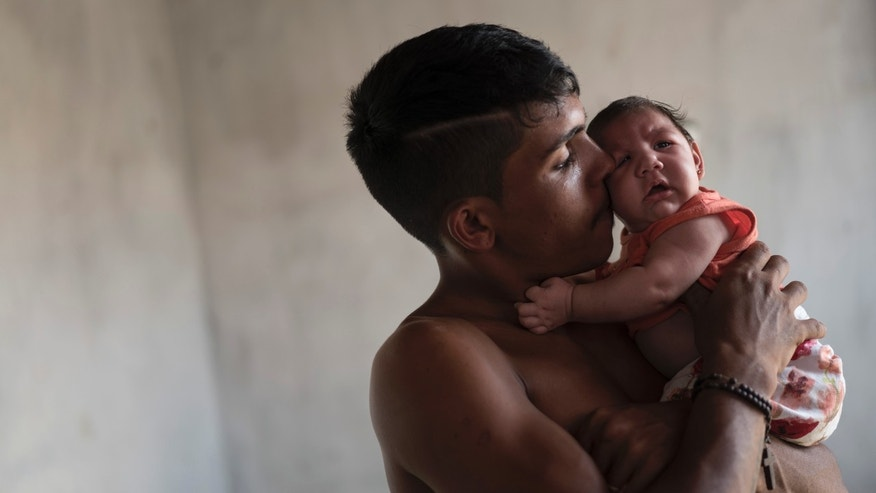 In this Dec. 23, 2015 photo,  Dejailson Arruda holds his daughter Luiza at their house in Santa Cruz do Capibaribe, Pernambuco state, Brazil. More than 2,700 babies have been born in Brazil with microcephaly this year, up from fewer than 150 in 2014. Brazilâs health officials say theyâre convinced the jump is linked to a sudden outbreak of the Zika virus that infected Pereira, though international experts caution itâs far too early to be sure. (AP Photo/Felipe Dana)