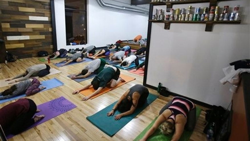 This Thursday, Dec. 3, 2015 photo shows participants practicing yoga at the Platform Beer Co., in Cleveland. Craft breweries are partnering up with yoga studios around the country as more breweries are hosting classes to attract a new crowd to the bars and yoga studios are using the beer to get more men to try yoga. (AP Photo/Tony Dejak)